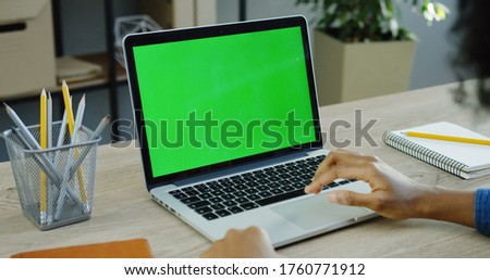 Over shoulder view on male hands working on the laptop computer which is on the white wooden table in the office. Green screen. Chroma key. Close up
