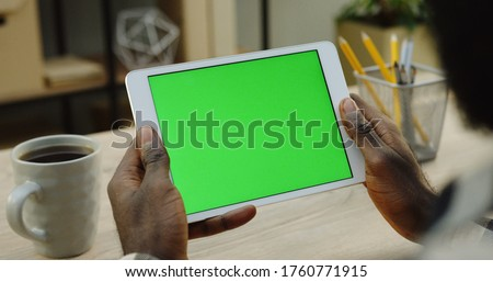 Over shoulder view on the white tablet computer holded by african american man horizontally. Fingers scrolling and taping on it. Green screen. Chroma key. Wooden office desk with cup of coffee