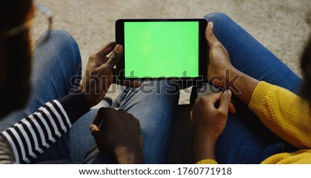 African American couple holding a black tablet device with green screen horizontally and woman scrolling and taping on it. Chroma key. Over shoulder. Close up