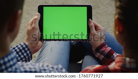 Over shoulder view on the Caucasian couple sitting with a black horizontal tablet computer and watching on it. Green screen. Chroma key