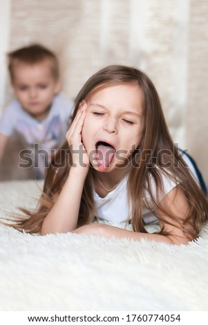 Funny and humorous photo of a little girl sister who makes faces and sticks out her tongue because she is being naughty and doesn't want to play with her brother crawling towards her. Impish children
