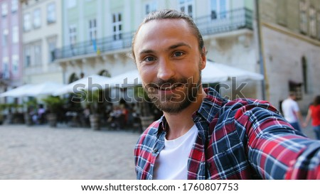 Close up portrait of attractive man with beard possing on camera while making photo or video on the city background.