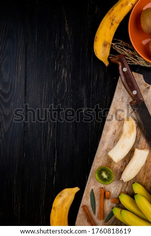 top view of banana fruit with almond, cinnamon sticks and old kitchen knife on a wooden cutting board on black background with copy space #1760818619