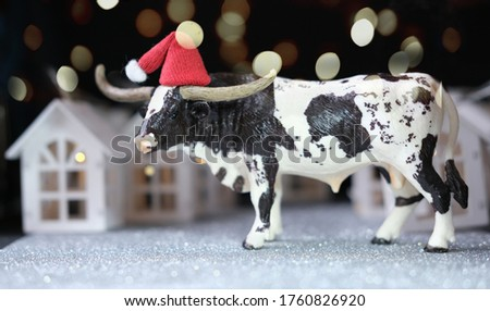 toy bull as symbol of 2021 year. happy new year concept. the ox and toy houses with bokeh lights. cow in a santa's red hat. chinese zodiac character bull.