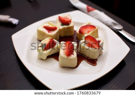 Japanese cuisine, dessert, sweet sushi rolls with banana fruit, kiwi cream cheese wrapped in pancake batter, decorated with a piece of strawberry and poured with strawberry syrup, served on a white pl