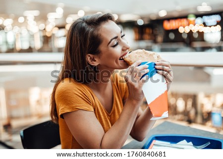 Beautiful and happy brunette woman sitting in restaurant and enjoying in eating delicious handmade pancakes or crepes. Royalty-Free Stock Photo #1760840681