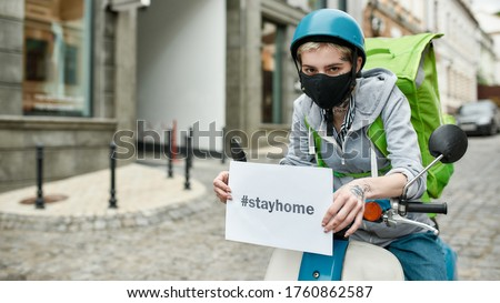 Young delivery woman in mask with thermo backpack holding a card with the inscription Stay Home, delivering food on a motor scooter. Courier, delivery service, lockdown concept. Focus on face and card
