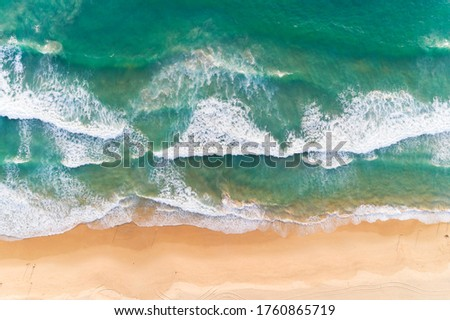 Aerial view sandy beach and crashing waves on sandy shore Beautiful tropical sea in the morning summer season image by Aerial view drone shot, high angle view Top down Royalty-Free Stock Photo #1760865719