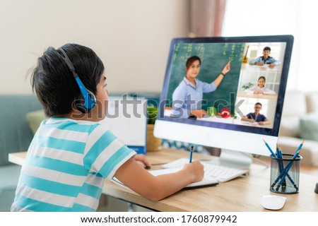 Asian boy student video conference e-learning with teacher and classmates on computer in living room at home. Homeschooling and distance learning ,online ,education and internet. #1760879942