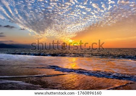 A Sailboat is sailing Along the Ocean at Sunset Royalty-Free Stock Photo #1760896160