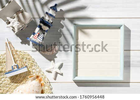 Top view summer rustic picture frame and lighthouse,seashell decorate on white wooden table with sunlight shade