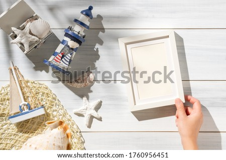 Top view hand lying summer rustic picture frame and lighthouse,seashell decorate on white wooden table with sunlight shade