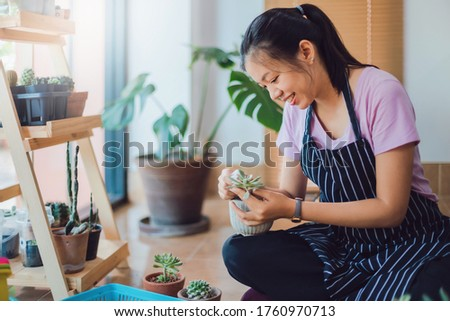 Asian young woman wearing apron caring for green indoor plant at home.New normal lifestyle concept of Hobby during quarantine and social distancing to stop spread disease of Coronavirus. Royalty-Free Stock Photo #1760970713