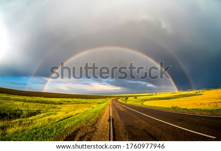 Rainbow over rural road landscape. Rainbow road view. Rainbow road landscape #1760977946