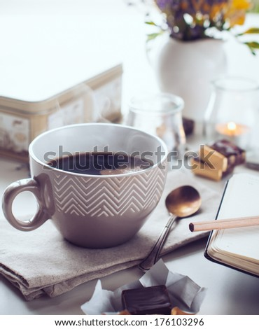 A cup of hot coffee, sweets, candles and flowers. Morning background. #176103296