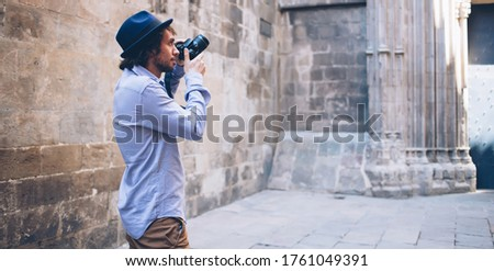Side view of stylish adult photographer in casual clothes and hat looking away and searching better foreshortening while standing on street against blurred exterior of shabby medieval building