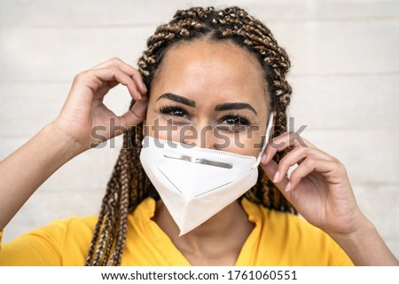 African woman with braids wearing face medical mask - Young girl using facemask for preventing and stop corona virus spread - Healthcare medical and youth millennial people concept  Royalty-Free Stock Photo #1761060551