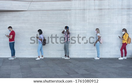 Group of young people waiting for going inside a shop market while keeping social distance in line during coronavirus time - Protective face mask and spread virus prevention - Main focus on black man Royalty-Free Stock Photo #1761080912