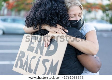 Young african woman hugging a white northern woman after a protest - Northern woman with end racism bannner in her hands - Concept of no racism  Royalty-Free Stock Photo #1761088373
