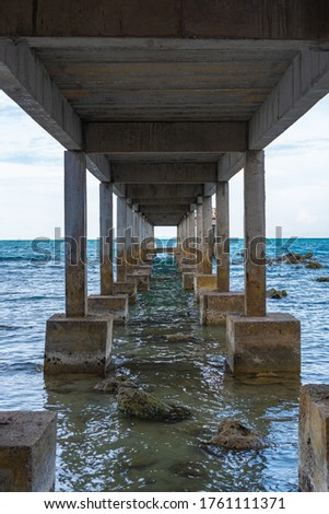 vertical photo, inside view, concrete bridge on the island of Koh Samui in Thailand at low tide, pier for mooring ships, building on the south coast of the island #1761111371