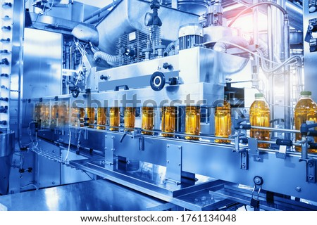 Beverage factory, Conveyor belt with juice in bottles, Industrial Interior in blue color, food and drink production line process. Royalty-Free Stock Photo #1761134048