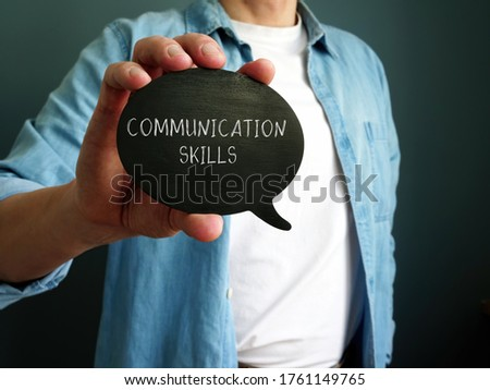 Young guy shows handwritten inscription Communication Skills. Royalty-Free Stock Photo #1761149765