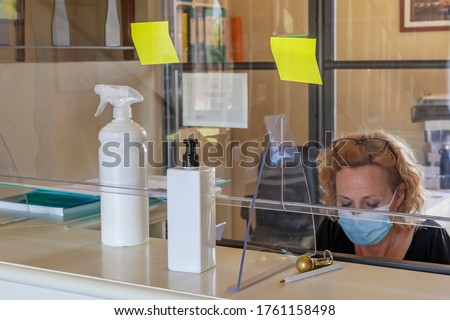 The new way of working imposed by the needs to avoid possible contagions from Covid-19 coronavirus, with plexiglass screen and mask Royalty-Free Stock Photo #1761158498