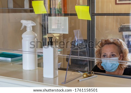 The new way of working imposed by the needs to avoid possible contagions from Covid-19 coronavirus, with plexiglass screen and mask Royalty-Free Stock Photo #1761158501