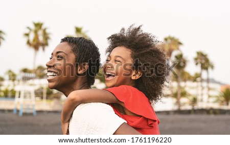 Happy African family on the beach during summer holidays - Afro American people having fun on vacation time - Parents love and travel lifestyle concept Royalty-Free Stock Photo #1761196220