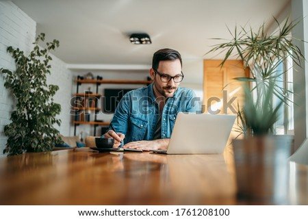 Handsome man taking notes and looking at laptop, at home office, portrait. #1761208100