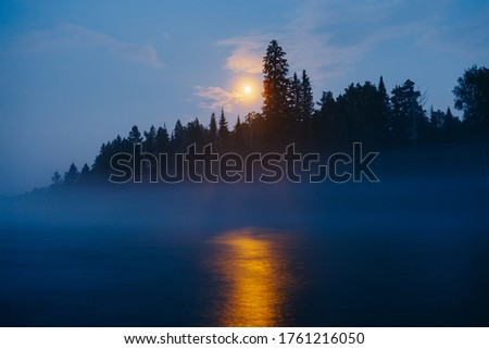Moonrise over dark foggy forest with moonbeam in river. Dark blue midnight nature landscape with orange light over water from moon. Mystical natural scenery in Altai Republic, Siberia, Russia #1761216050