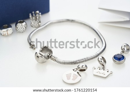Beautiful stylish bracelet with silver charm beads with gems, isolated on white background. Assorted metal charm pendants for necklace or bracelet. Women accessories. Royalty-Free Stock Photo #1761220154
