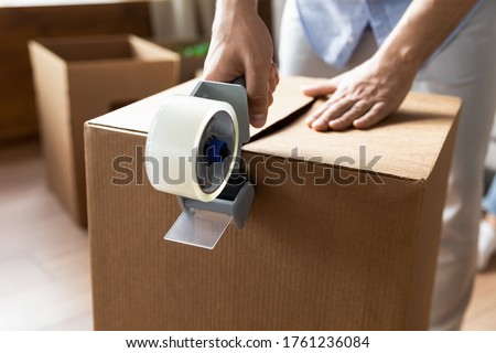 Close up man sealing cardboard box with adhesive tape, using dispenser, moving day and relocating delivery service concept, young male preparing to relocation, packing belongings, parcel Royalty-Free Stock Photo #1761236084