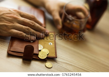 Fired man countsing his last money to drink expensive alcohol. Wrinkled alcoholic sits at brown wooden table with a glass of cognac with ice, on the table, empty wallet with coins Royalty-Free Stock Photo #1761245456