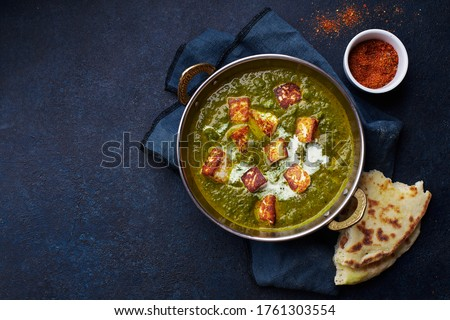 Flat lay top view of vegetarian palak paneer starter. Indian cuisine, curry dish with soft cheese and spinach on concrete background with copy space Royalty-Free Stock Photo #1761303554
