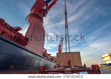 Package unit of the heavy life cargo being discharging or loading by the ship crane under supervisor by professional handling in the port terminal Royalty-Free Stock Photo #1761315413