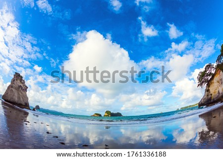 Mirror reflections of clouds in wet sand. Cathedral Cove on the North Island of New Zealand. Photo taken with fisheye lens. The concept of exotic, ecological and photo tourism