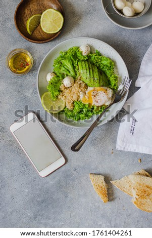 green salad bowl with quinoa, mozzarella, avocado, poached egg, lettuce, lime and olive oil searved on gray stone background with empty phone screen. healthy eating concept. flatlay with copyspace