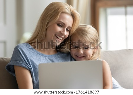 Close up loving caring mother spend time with little daughter at home, sit on couch having fun using internet websites, watching cartoons, learn educational app, choose e-commerce goods and services