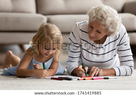 Old caring grandma spend time well lie on warm floor with little grandkid multi-generational family drawing pictures hold colored felt-tip pens. Pastime at modern home with underfloor heating concept