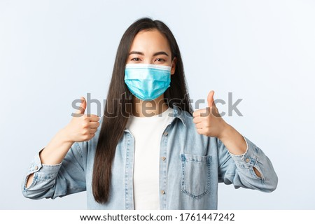 Social distancing lifestyle, covid-19 pandemic everyday life and leisure concept. Supportive enthusiastic asian woman in medical mask thumbs-up, wearing PPE while going grocery shopping #1761447242