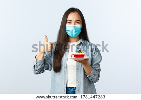 Social distancing lifestyle, covid-19 pandemic, celebrating holidays during coronavirus concept. Happy smiling asian birthday girl in medical mask, show bday cake and thumb-up pleased