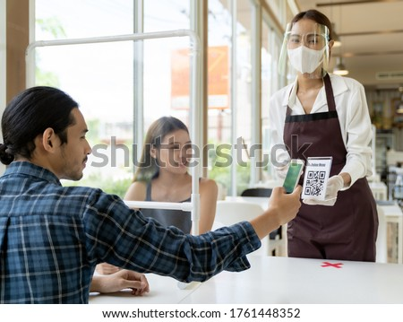 Asian customer scan QR code online menu from waitress with face mask and face shield. Customer sat on social distancing table for new normal lifestyle in restaurant after coronavirus covid-19 pandemic #1761448352