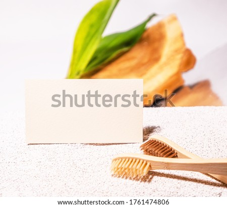 Cosmetology business card mock up with bamboo toothbrushes. Eco natural style. Cement and green leaf. Beauty clinic card. Still life style. White backgound