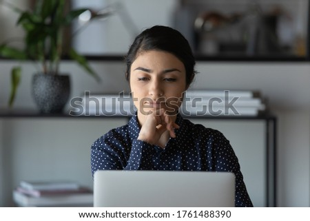 Frustrated upset Indian ethnicity woman employee office worker sit at workplace desk leaned chin on hand looking at laptop screen thinking over problem solution, wait e-mail feels tired and overworked #1761488390