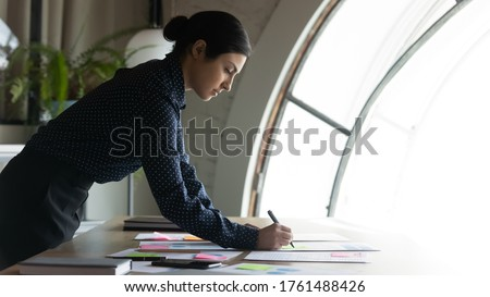 Project management statistics, strategizing and forecasting concept. Focused Indian ethnicity businesswoman do financial stats analysis writing data make overview preparing for negotiations or seminar