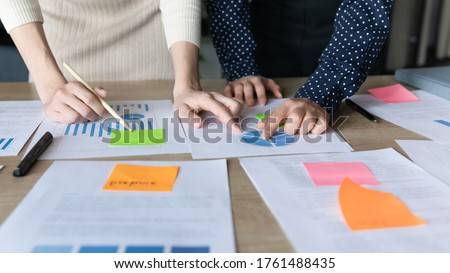 Close up businesswomen analyzing project stats reviewing information and data on charts shown on papers financial report, make overview attach post-it writing notes, explanations, forecasting concept Royalty-Free Stock Photo #1761488435