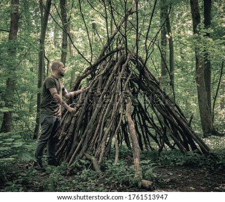 Man building a  survival  shelter in the forest. Shelter in the woods from tree branches. Royalty-Free Stock Photo #1761513947