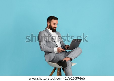 Handsome businessman using laptop computer while sitting on chair against blue background