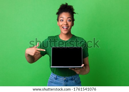 Excited african girl presenting laptop with black blank screen for mock up, isolated on green studio wall, empty space